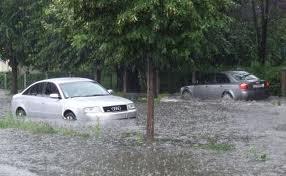Inundaţii pe strada Industriilor, o maşină a rămas blocată